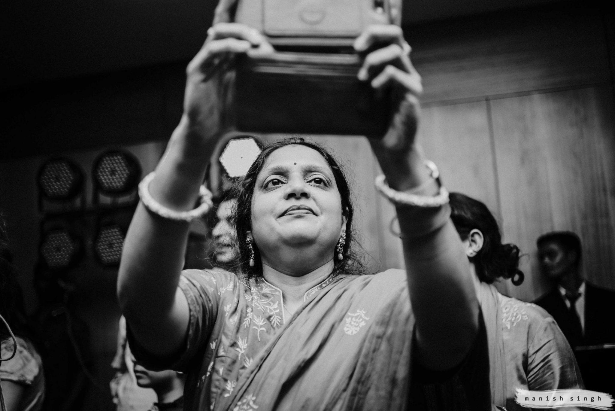 Guest taking photos in Odisha wedding sangeet